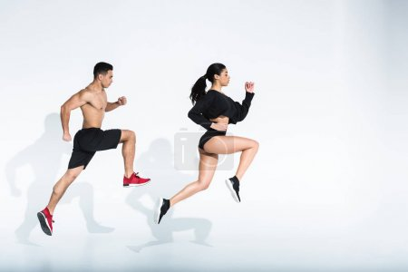 Photo for Side view of sportive african american girl and athletic mixed race man running on white background - Royalty Free Image