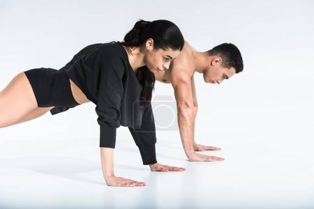 Photo for Side view of pretty african american girl and handsome mixed race man doing push ups on white - Royalty Free Image