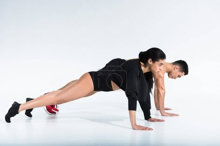 Photo for Side view of sportive multicultural man and woman doing push ups on white - Royalty Free Image