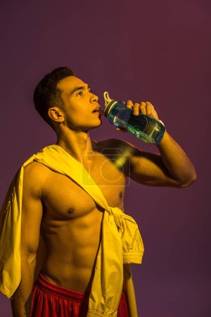 Photo for Handsome sportive mixed race man drinking from sport bottle on purple background - Royalty Free Image