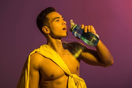 Photo for Good-looking sportive mixed race man drinking from sport bottle on purple background - Royalty Free Image