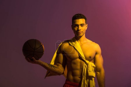 Photo for Handsome sportive mixed race man holding brown ball on purple background - Royalty Free Image