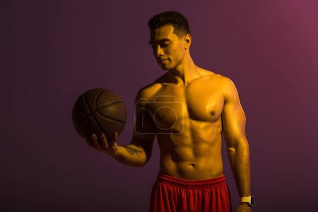 Photo for Handsome athletic mixed race man holding brown ball on purple background - Royalty Free Image