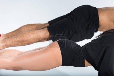 Photo pour Vue partielle de l'homme et de la femme faisant push ups sur le fond blanc - image libre de droit