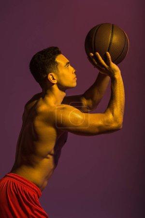 Foto de Guapo hombre de carreras mixtas deportiva jugando a la pelota en el fondo púrpura - Imagen libre de derechos