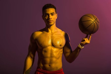 good-looking sportive mixed race man holding brown ball and looking at camera on purple background