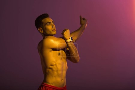 Photo pour Handsome sportive man in smart watch stretching on purple background - image libre de droit