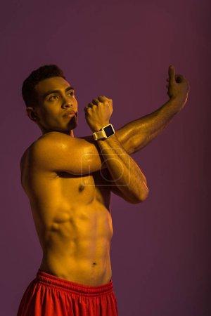 Photo pour Beau homme de course mixte athlétique dans la montre intelligente s'étendant sur le fond pourpre - image libre de droit