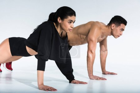 Photo for Sportive multicultural woman and man doing push ups on white background - Royalty Free Image
