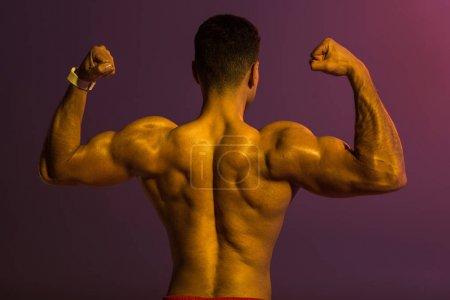 Photo pour Vue arrière de l'homme athlétique avec le torse musculaire démontrant des biceps sur le fond pourpre - image libre de droit