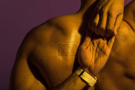 Photo for Back view of athletic man with muscular torso stretching isolated on purple - Royalty Free Image