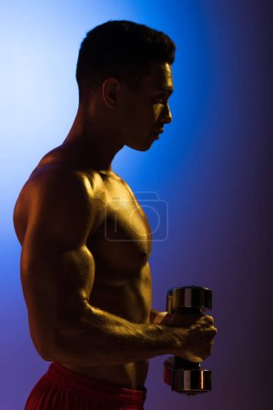 Photo for Side view of athletic mixed race man with dumbbells on blue and dark purple gradient background - Royalty Free Image