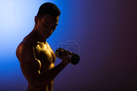 Photo for Handsome athletic mixed race man training with dumbbell on blue and dark purple gradient background - Royalty Free Image