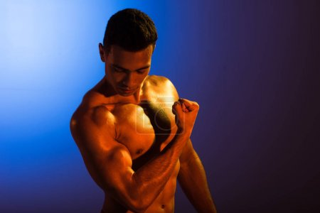 Photo for Handsome athletic mixed race man demonstrating biceps on blue and dark purple gradient background - Royalty Free Image