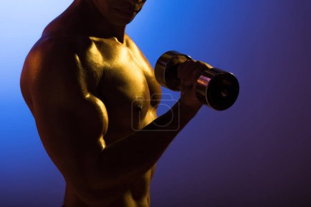 Photo for Cropped view of athletic man with dumbbell on blue and dark purple gradient background - Royalty Free Image