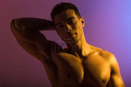 Photo for Good-looking sportive mixed race man posing at camera on purple and blue gradient background - Royalty Free Image