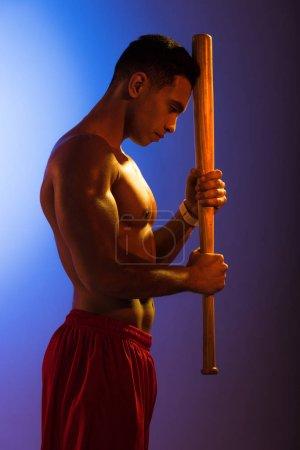 Foto de Guapo hombre de carreras mixtas con torso muscular sosteniendo bate de béisbol en el fondo degradado azul y púrpura oscuro - Imagen libre de derechos