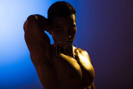 Foto de Handsome athletic mixed race man posing at camera on blue and dark purple gradient background - Imagen libre de derechos