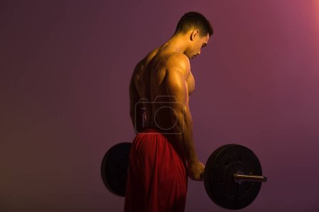 Photo for Sportive mixed race man in red shorts holding barbell on purple background - Royalty Free Image