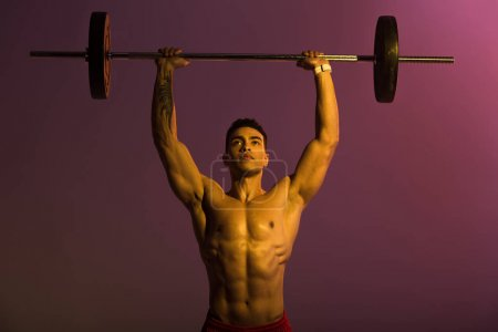 Photo for Handsome athletic mixed race man lifting barbell on purple background - Royalty Free Image