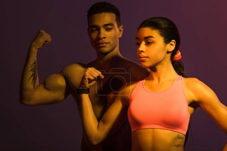 Photo for Sportive african american woman and athletic mixed race man demonstrating biceps on dark background - Royalty Free Image