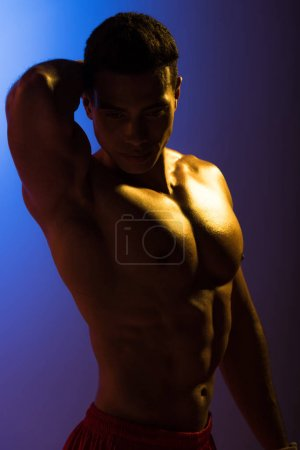 Foto de Guapo hombre de carreras mixtas con torso muscular posando en la cámara en el fondo degradado azul y púrpura oscuro - Imagen libre de derechos