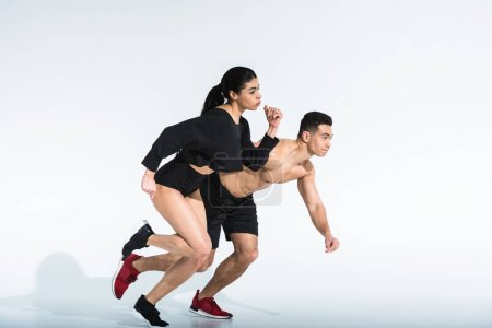 Photo for Sportive multicultural woman and man in black sportswear running on white background - Royalty Free Image