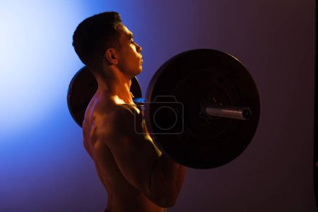 Photo for Handsome athletic man lifting barbell on blue and dark purple gradient background - Royalty Free Image