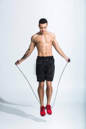 Photo pour Beau sportif homme de course mixte sautant avec la corde à sauter sur le blanc - image libre de droit