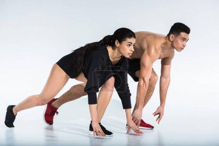 Photo pour Fille américaine africaine sportive et homme de course mixte athlétique restant dans la position de commencement sur le blanc - image libre de droit