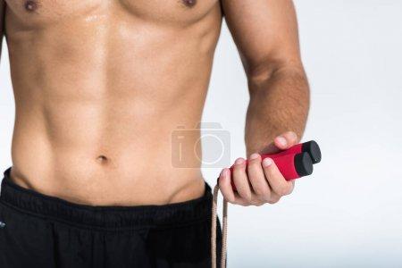Photo pour Vue recadrée de l'homme avec la corde de saut de fixation de torse musculaire sur le blanc - image libre de droit