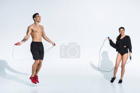 Photo pour Fille américaine africaine de sourire et formation mélangée belle d'homme de course avec des cordes de saut sur le fond blanc - image libre de droit