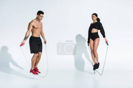 Photo for Athletic mixed race man and sportive african american woman jumping with skipping ropes on white - Royalty Free Image