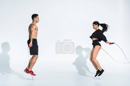 Photo pour Sportive multicultural man and woman jumping with skipping ropes on white - image libre de droit