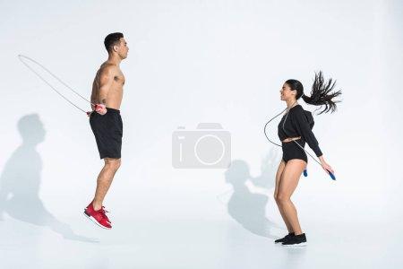 Photo pour Femme américaine africaine de sourire et formation mélangée athlétique d'homme de course avec des cordes de saut sur le blanc - image libre de droit