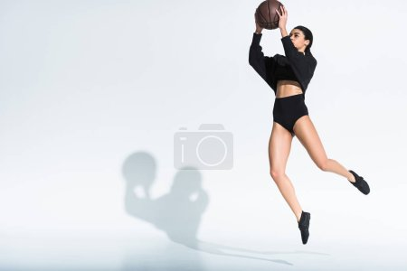 Photo for Sportive african american girl in black sportswear and sneakers jumping with ball on white background - Royalty Free Image