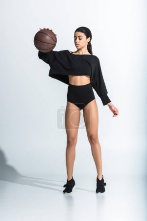 Photo for Attractive sportive african american girl in black sportswear and sneakers playing ball on white - Royalty Free Image