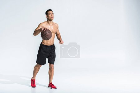 Photo for Handsome athletic mixed race man in black shorts and red sneakers playing ball on white - Royalty Free Image