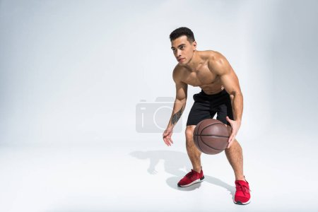 Photo for Handsome sportive mixed race man in red sneakers playing ball on white - Royalty Free Image