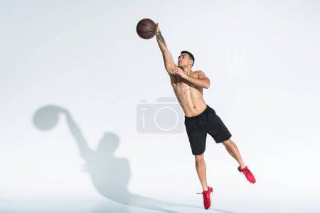 Photo for Handsome mixed race man in black shorts and red sneakers jumping with ball on white - Royalty Free Image