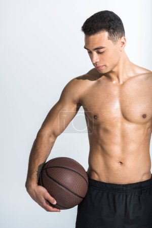 Photo for Handsome sportive mixed race man with muscular torso holding brown ball on white - Royalty Free Image
