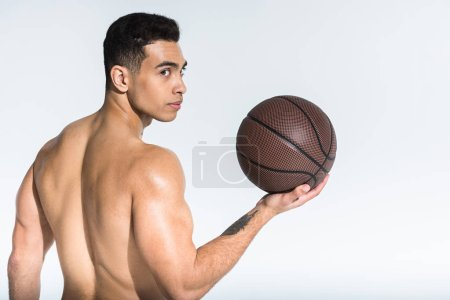 Photo for Handsome athletic mixed race man with muscular torso holding brown ball on white - Royalty Free Image