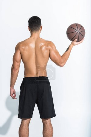 Photo for Back view of athletic man in black shorts holding brown ball on white - Royalty Free Image