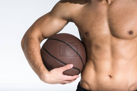 Photo for Cropped view of athletic man with muscular torso holding brown ball on white - Royalty Free Image