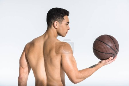 Photo for Athletic mixed race man with  muscular torso holding brown ball on white - Royalty Free Image