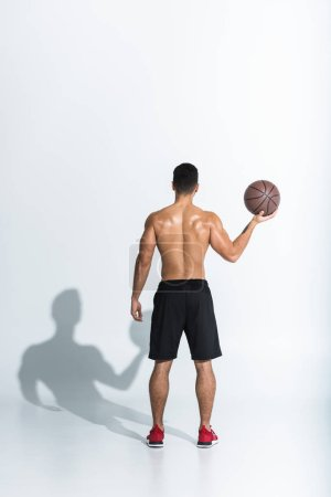 Photo for Back view of athletic man in black shorts holding brown ball on white background - Royalty Free Image