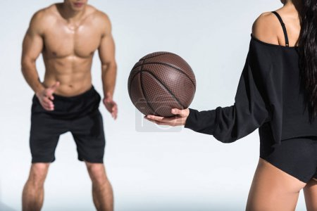 Photo pour Cropped view of shirtless man with muscular torso near sportive african american girl holding ball on white - image libre de droit