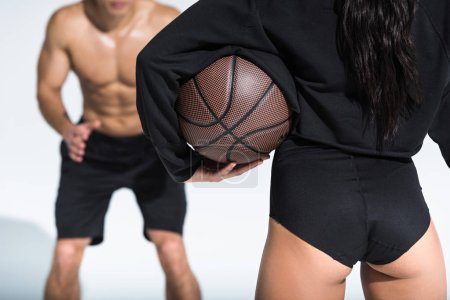 Photo for Partial view of sportive girl holding brown ball near athletic shirtless man on white - Royalty Free Image