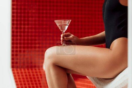 Photo pour Vue partielle de la fille en maillot de bain tenant verre de martini dans le centre de spa - image libre de droit