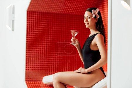 Photo pour Fille de sourire avec la fleur dans le verre de fixation de cheveux de martini dans le centre de spa - image libre de droit